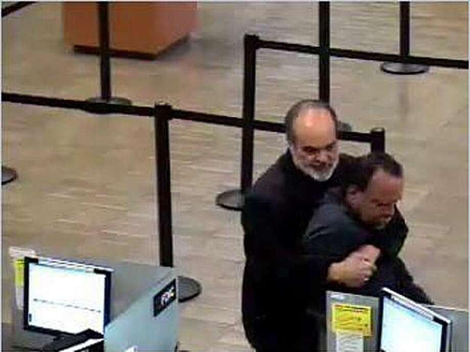 A bank surveillance camera captures an image of former San Francisco Chronicle photographer Kim Komenich holding bank robbery suspect Victor Anthony Fernandes in a bear hug at a Wells Fargo branch in San Jose, Calif., on Monday, April 12, 2010. Photo: San Jose Police Department