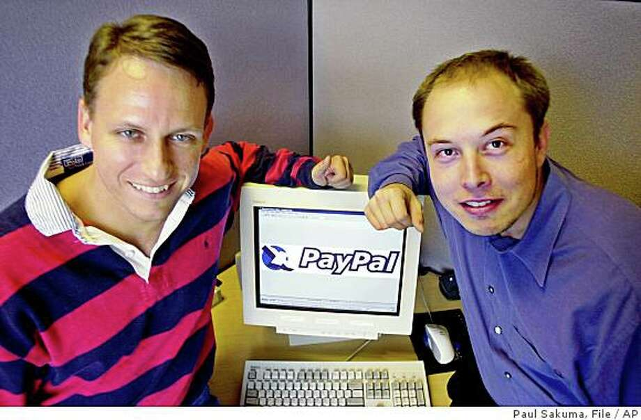FILE--PayPal Chief Executive Officer Peter Thiel, left, and founder Elon Musk, right, pose with the PayPal logo at corporate headquarters in Palo Alto, Calif., on Oct. 20, 2000. Photo: Paul Sakuma, File, AP