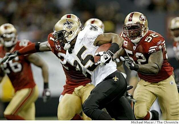 New Orleans Saints Reggie Bush (25) sweeps left in the 2nd quarter chased by San Francisco 49ers Patrick Willis (52) and San Francisco 49ers Walt Harris (27) as the San Francisco 49ers lost to the New Orleans Saints  31-17, in NFL action at the New Orleans Superdome in New Orleans, La.  on Sunday Sept. 28, 2008. Photo: Michael Macor, The Chronicle