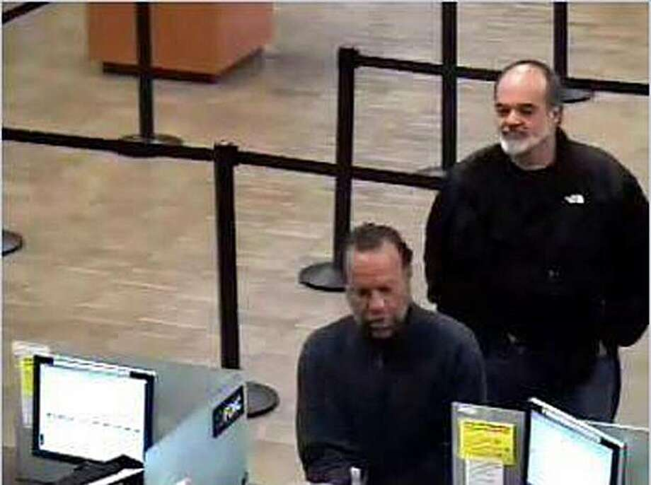 A bank surveillance camera captures an image of former San Francisco Chronicle photographer Kim Komenich (right) waiting in line behind bank robbery suspect Victor Anthony Fernandes at a Wells Fargo branch in San Jose, Calif., on Monday, April 12, 2010. Photo: San Jose Police Department