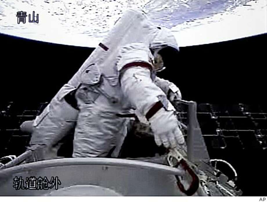 In this video grab taken at the Beijing Space Command and Control Center released by China's Xinhua News Agency, Saturday, Sept. 27, 2008, Chinese astronaut Zhai Zhigang walks out of the orbit module of the Shenzhou-7 spacecraft for a spacewalk. (AP Photo/Xinhua) Photo: AP