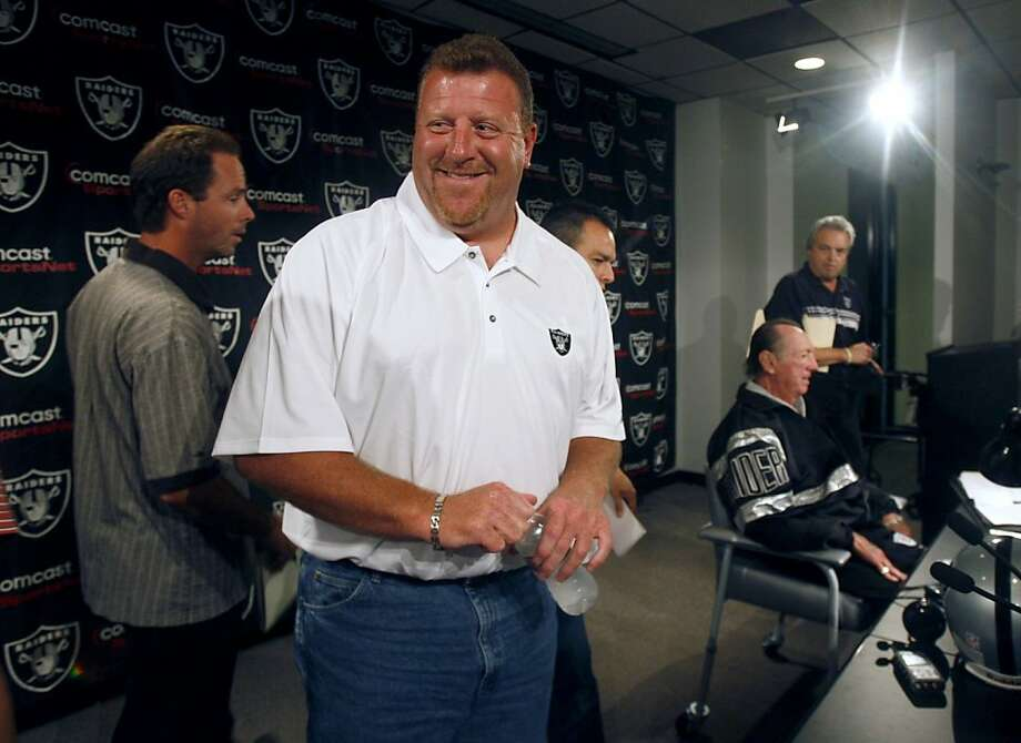 Offensive line coach Tom Cable smiles after a news conference held by Oakland Raiders owner Al Davis, lower right, to name Cable as the interim head coach at the team's headquarters in Alameda, Calif., on Tuesday, Sept. 30, 2008. Photo: Paul Chinn, The Chronicle