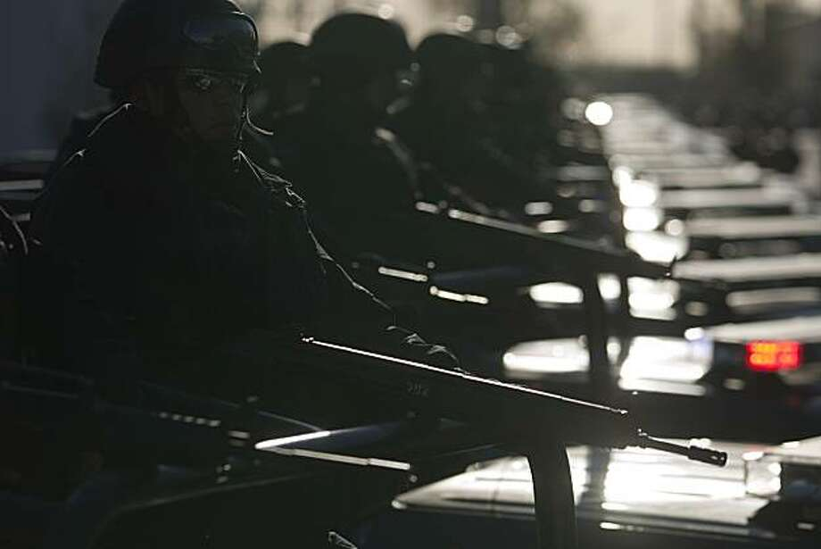 Federal police stand in formation on the back of trucks as they begin their patrols in Ciudad Juarez, Mexico, Thursday, April 8, 2010.  The federal police are taking the lead of the city's security which was headed by the army in recent months. Photo: Guillermo Arias, Associated Press