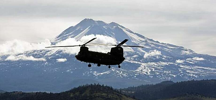 A California Air National Guard Chinook helicopter returns to the Weed Airport after dropping off search and rescue personnel on a snow field near The Summit of Mt. Shasta near Weed, Calif. Rangers found the body of 26-year-old Thomas Bennett of Oakland in a snow cave where his friend had left him before going for help, the Siskiyou County Sheriff's Office said. Rescuers had been trying to reach Bennett since his climbing partner Mark Thomas, 26, of Berkeley, called 911 Sunday to report that Bennett had collapsed near the summit. The two experienced climbers were trapped Saturday night by severe winds. Photo: Andreas Fuhrmann, AP