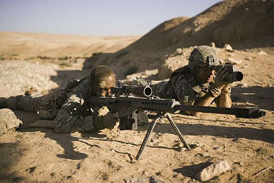Sgt. JT Sanborn (Anthony Mackie, left) mans the Barrett .50 caliber sniper rifle as Staff Sgt. Will James (Jeremy Renner, right) spots.   (Left to right) ANTHONY MACKIE and JEREMY RENNER star in THE HURT LOCKER. Photo: Jonathan Olley, Summit Entertainment