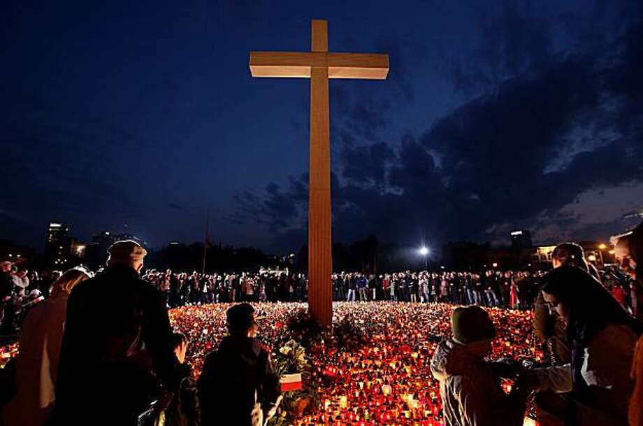 WARSAW, POLAND - APRIL 11:  Mourners arrive to light candles under a giant cross at Pilsudski Square in memory of late Polish President Lech Kaczynski on April 11, 2010 in Warsaw, Poland. Kaczynski, his wife Maria and leading members of the Polish military and government were killed when the presidential plane they were travelling in crashed while attempting to land at Smolensk, Russia, the day before. The delegation was on its way to attend memorial services for the thousands of Polish military officersmurdered by the Soviets during World War II at Katyn. Photo: Sean Gallup, Getty Images