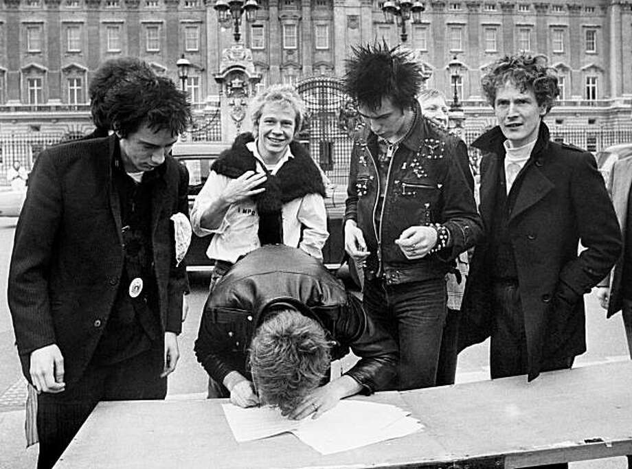 In this March 1977 file photo, the Sex Pistols, from left: Johnny Rotten, Steve Jones (signing document), Paul Cook,  Sid Vicious and their manager Malcolm McLaren sign a new recording contract outside Buckingham Palace in London. The former manager of the Sex Pistols and one of the seminal figures of the punk rock era, Malcolm McLaren, died Thursday, April 8, 2010 his son said. He was 64. (AP Photo/Press Association)  UNITED KINGDOM OUT; ARCHIVE OUT; FOR USE IN NORTH AMERICA ONLY Photo: AP
