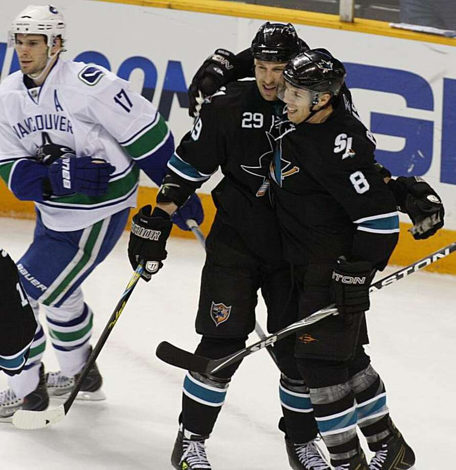San Jose Sharks' Joe Pavelski (8) celebrates with Ryane Clowe (29) after scoring a goal against the Vancouver Canucks during the first period of an NHL hockey game Thursday, April 8, 2010, in San Jose, Calif. Canucks' Ryan Kesler is at left. Photo: George Nikitin, AP
