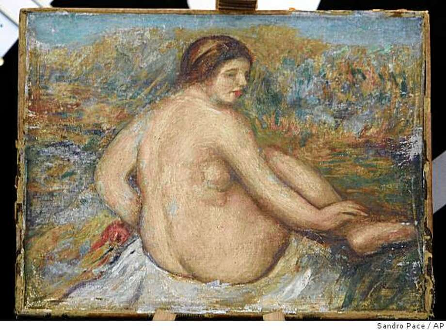 Italian Carabiniere, paramilitary police, display  a painting by impressionist master Pierre-Auguste Renoir during a press conference in Rome, Friday, Sept. 26, 2008. The painting was stolen in 1975 from a restorer's studio in Milan. The French artist's portrait of a naked woman was located this summer after those who held it contacted an Italian art critic to have its value appraised before selling it. (AP Photo/Sandro Pace) Photo: Sandro Pace, AP