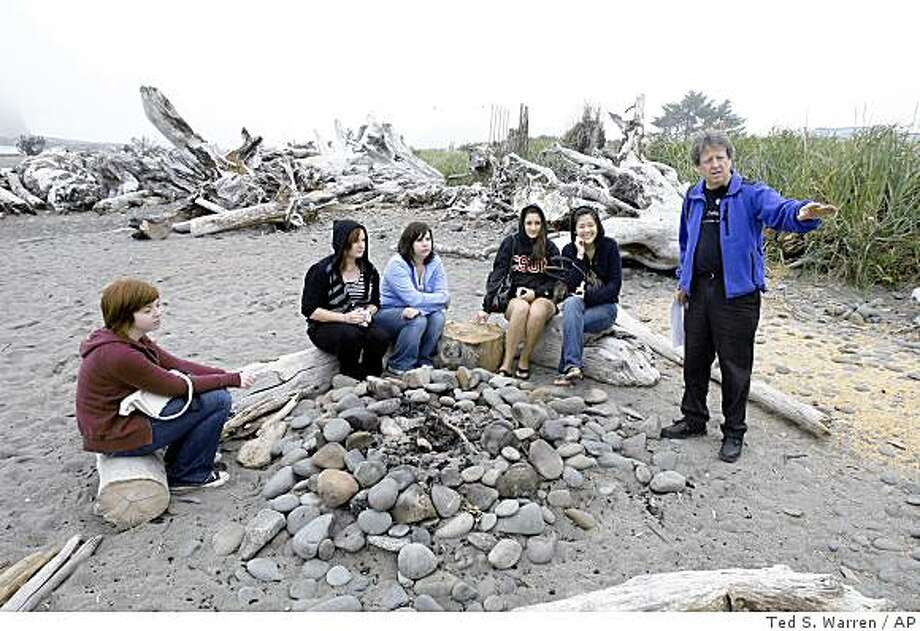 """** ADVANCE FOR SUNDAY, SEPT. 21 ** Visitors listen Friday, Sept. 5, 2008, to Michael Gurling, right, of the Forks, Wash., Chamber of Commerce, talk about the bonfire location on a beach in LaPush, Wash., that is portrayed as the place where Bella Swan, the main character in author Stephenie Meyer's vampire-themed """"Twilight"""" books, learns that her high-school friend Edward Cullen is really a vampire. The visitors were taking part in a """"Twilight Tour"""" led by Gurling that takes fans of the books, which are set in the nearby town of Forks, Wash., around to locations central to the plot and characters. The attention is welcome in Forks, which has long suffered by the decline in the timber industry. (AP Photo/Ted S. Warren) Photo: Ted S. Warren, AP"""