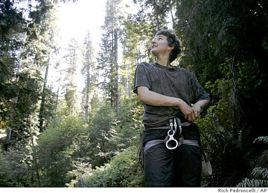 """Nadia Berg looks up at the giant redwood tree she has lived in for 11 months after rappelling down the more than 1,500-year-old redwood she has called home in the Nanning Creek grove near Scotia, Calif., Thursday, Sept. 18, 2008. Berg lived 200 feet above the ground in the tree, she called """"Grandma,"""" to prevent it and others in the grove from being cut down. Berg and fellow tree defender Billy Stoetzer have climbed out of their trees for good after an agreement had been reached between the new owners of the forest, Humboldt Redwood Co., and environmental activists to end the more than 20-year-old occupation of ancient trees and spare them from the saw. (AP Photo/Rich Pedroncelli) Photo: Rich Pedroncelli, AP"""