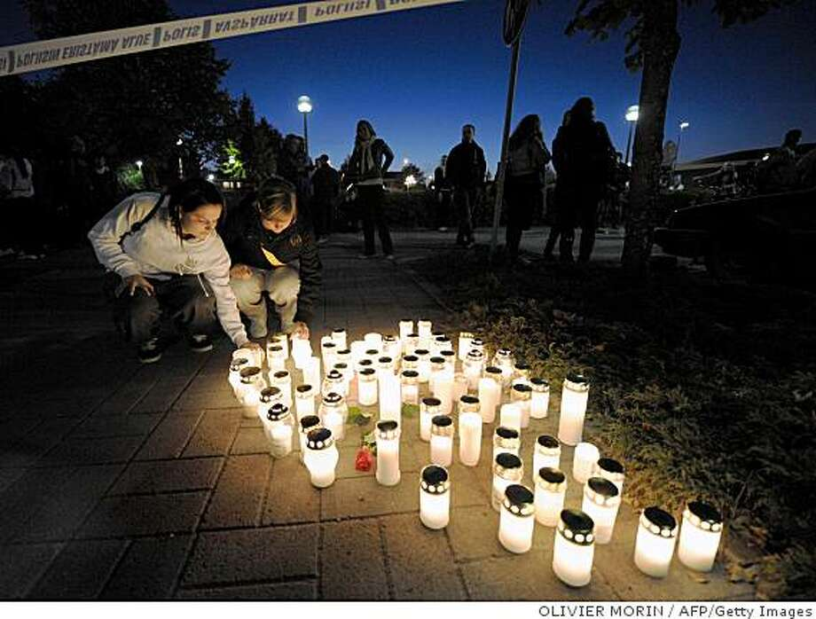 People lay candles in the evening at the Kauhajoki vocational high school in Kauhajoki, southwestern Finland, on September 23, 2008. A gunman went on a rampage for an hour and a half at the Kauhajoki vocational high school on the morning of September 23, killing at least 10 people before shooting himself in the head. The shooter -- identified by police as a second-year culinary arts student Matti Juhani Saari -- was clad in black clothes and a ski mask as he stalked the school looking for victims. AFP PHOTO/OLIVIER MORIN (Photo credit should read OLIVIER MORIN/AFP/Getty Images) Photo: OLIVIER MORIN, AFP/Getty Images