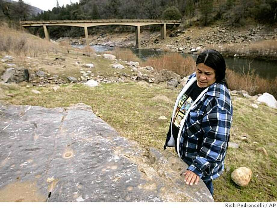 """Caleen Sisk-Franco,  leader of the Winnemen Wintu tribe, looks over """"pubity rock""""  that sits along the bank of of the McCloud River, near Shasta Lake, Calif., Friday,  Feb. 22, 2008.   The rock, where once a year Sisk-Franco and members of her tribe gather to celebrate the womanhood of their teenage girls,  is one of several tribal sacred spots that could be flooded over if Shasta Dam in enlarged.  Proposals to raise the 602- foot, concrete Shasta Dam, located in Northern California, are pitting water thirsty farmers against environmentalists and Democrats in the state Legilslature who oppose the project.(AP Photo/Rich Pedroncelli) Photo: Rich Pedroncelli, AP"""
