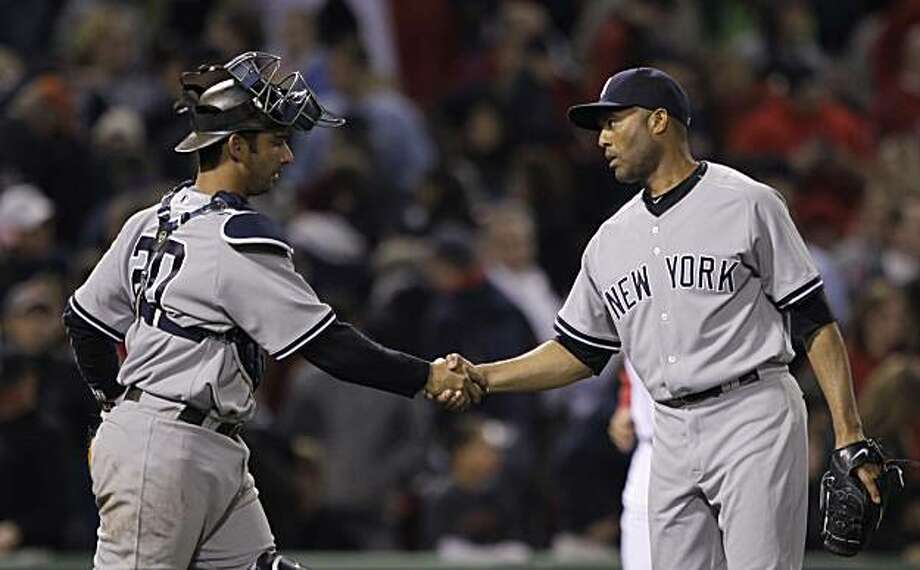 New York Yankees closer Mariano Rivera, right, is congratulated by teammate Jorge Posada, left, after earning his first save of the season against the Boston Red Sox during a baseball game Tuesday, April 6, 2010, in Boston.  The Yankees beat the Red Sox 6-4. Photo: Charles Krupa, AP
