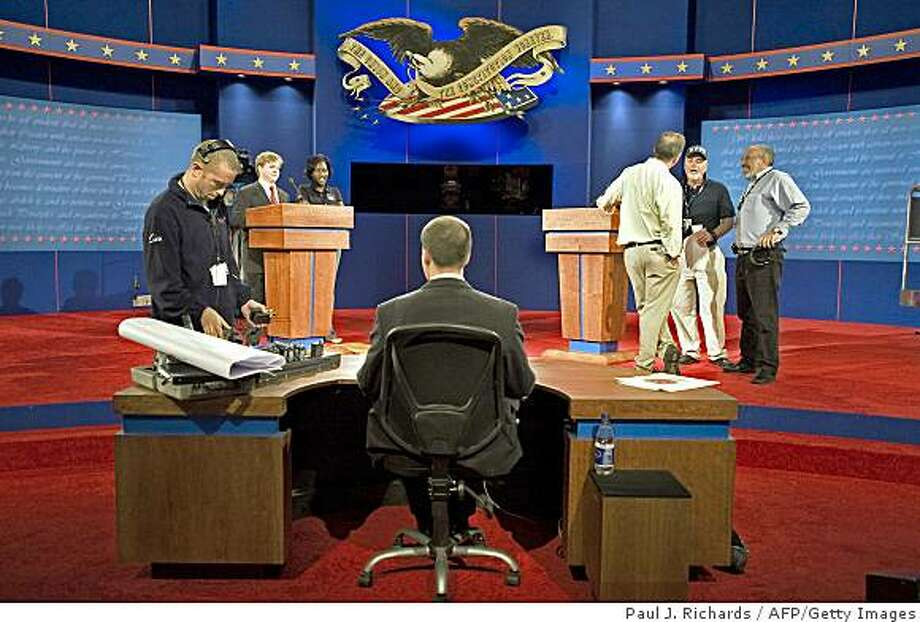 Stage and production crews make last minute adjustments to the set of the first presidential debate September 25, 2008 at the Ford Center in Oxford, Mississippi. The first debate is scheduled be in Oxford, MS, on September 26, then a Vice-Presidential debate in St. Louis Oct 2, followed by President debates in Nashville Oct 7, and Hempstead, NY Oct 15. The September 26 debate is in question as Arizona Sen. John McCain announced he would temporarily suspend campaigning to return to Washington to help with the agreement on a proposed $700 billion-dollar bailout of financial institutions before Congress.       AFP PHOTO/Paul J. Richards (Photo credit should read PAUL J. RICHARDS/AFP/Getty Images) Photo: Paul J. Richards, AFP/Getty Images