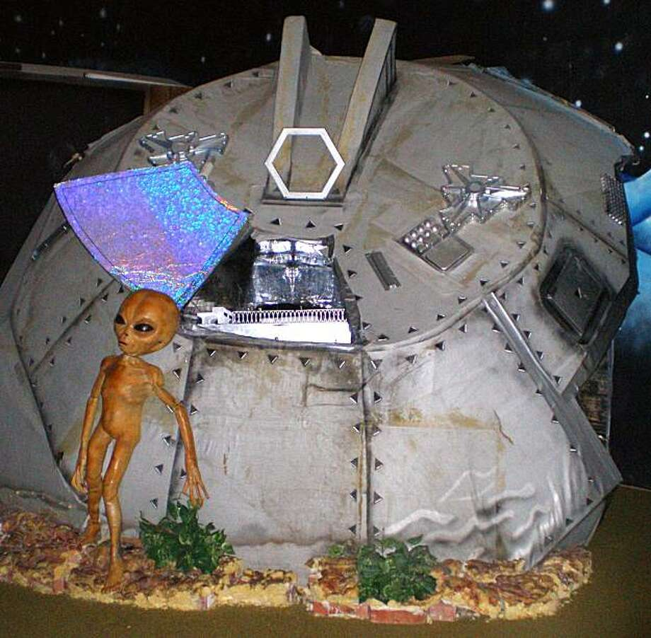 This photo taken in December 2006 at the Area 51 exhibit at the Alien Zone in Roswell, N.M., shows an alien standing outside a crashed spaceship. Photo: Justin Norton, AP