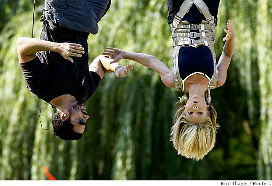 Magician David Blaine is interviewed by television personality Kelly Ripa while performing a stunt in Central Park in New York September 22, 2008. Blaine plans to hang upside down without a safety net for 60 hours. REUTERS/Eric Thayer (UNITED STATES) Photo: Eric Thayer, Reuters