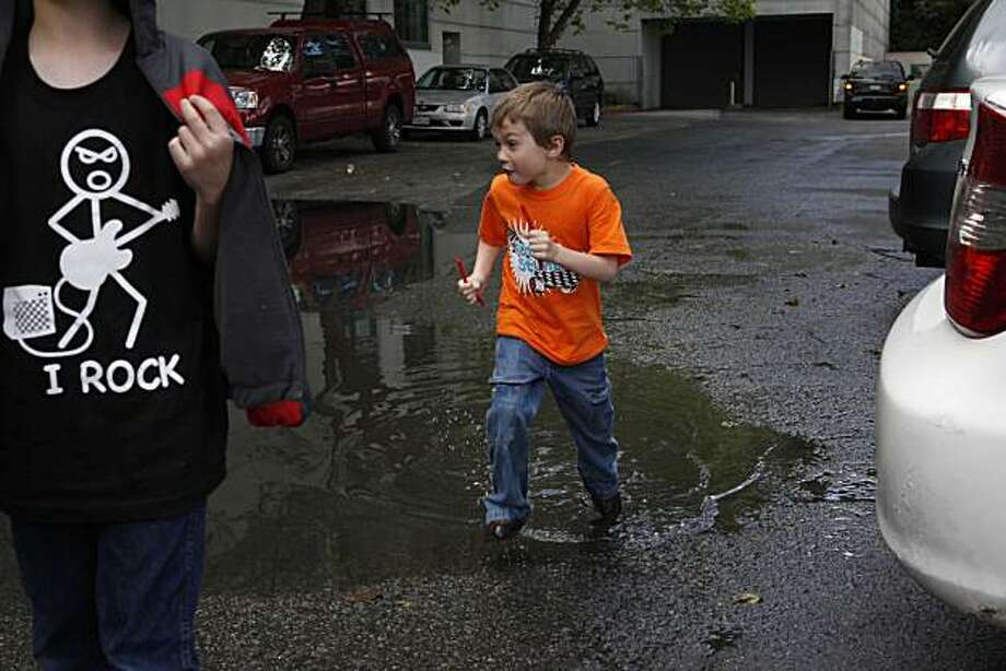 As erratic weather pattern confuse the Bay Area residents, Nate Carr, 5, of Provo Utah, runs through a puddle near Ghirardelli Square on Monday April 5, 2010 in San Francisco, Calif. Photo: Mike Kepka, The Chronicle