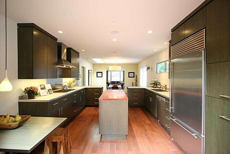 The open kitchen has a center island and built-in table, as well as Sub Zero, Fisher & Paykel and Bosch appliances. Photo: Courtesy Ron Susskind, Frank Howard Allen Realtors