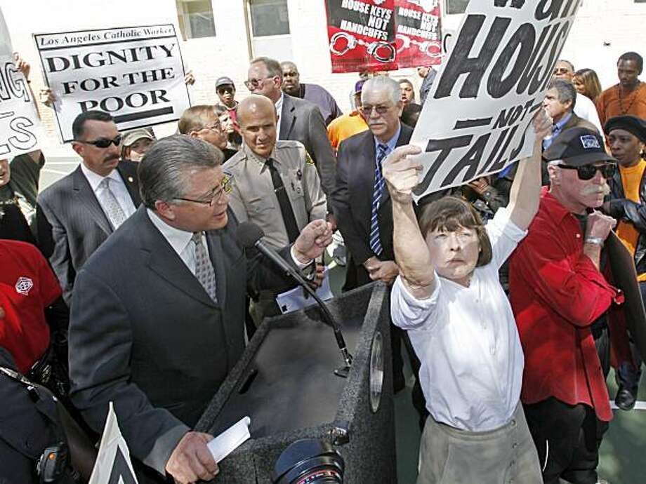 As demonstrators, including Alice Callaghan, right center, chant and hold signs, Los Angeles City Attorney Carmen Trutanich, at podium, announces the filing of a new civil injunction against several dozen individuals, many of them gang members, seeking torestrict narcotics activity in the Skid Row area of Los Angeles, at a news conference at Gladys Park in Skid Row Wednesday, April 7, 2010. Photo: Reed Saxon, AP