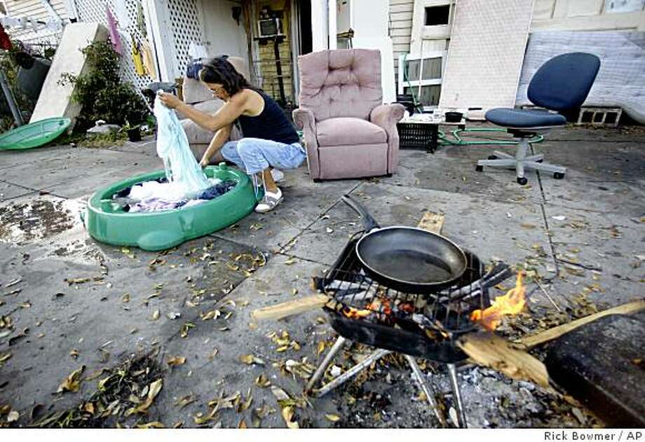 Galveston resident, Donna Lawe, who weathered Hurricane Ike at her home, is shown washing her clothes while preparing to cook breakfast Monday, Sept. 22, 2008, in Galveston, Texas. (AP Photo/Rick Bowmer Photo: Rick Bowmer, AP