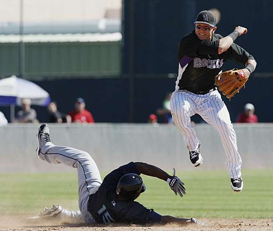 Colorado Rockies shortstop Troy Tulowitski, right, leaps to avoid the slide of Seattle Mariners' Milton Bradley after forcing him out at second on the front end of a double play in the fourth inning of a Cactus League spring training baseball game in Tucson, Ariz., on Sunday, March 14, 2010.  Seattle's Ryan Garko was out at first. Photo: Ed Andrieski, AP