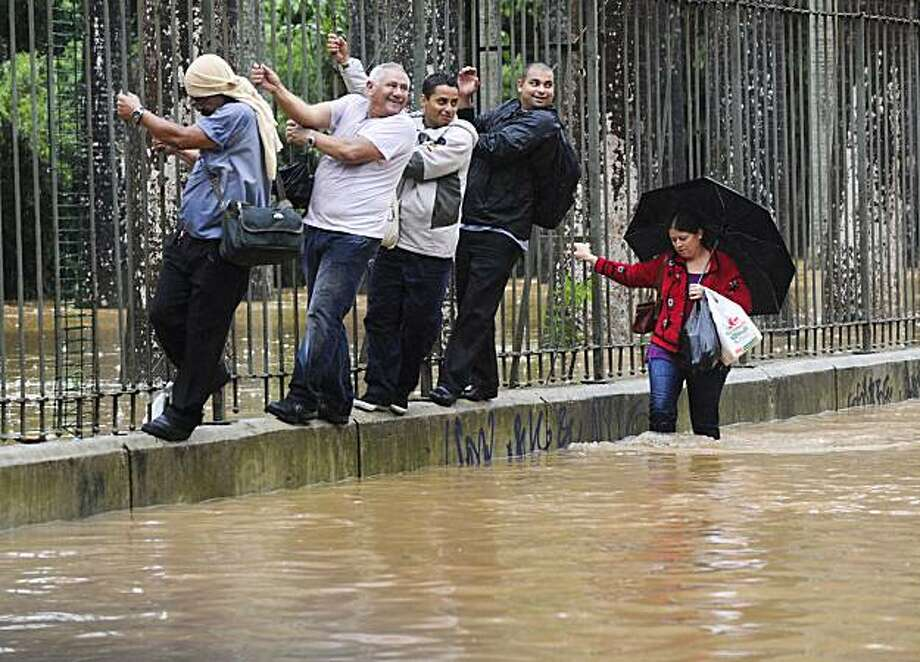 People walk along the wall while holding on to the railings of the Botanic Garden in an attempt to avoid getting their feet wet, in a flooded area of Rio de Janeiro, on April 6, 2010. Flooding from torrential rains and deadly mudslides claimed at least 77lives in Brazil's Rio de Janeiro state, authorities said Tuesday. Civil defense officials said about half of the fatalities occurred in Rio de Janeiro city, where authorities urged residents to remain indoors and not venture downtown, where streets wereimpassable. Photo: Antonio Scorza, AFP/Getty Images