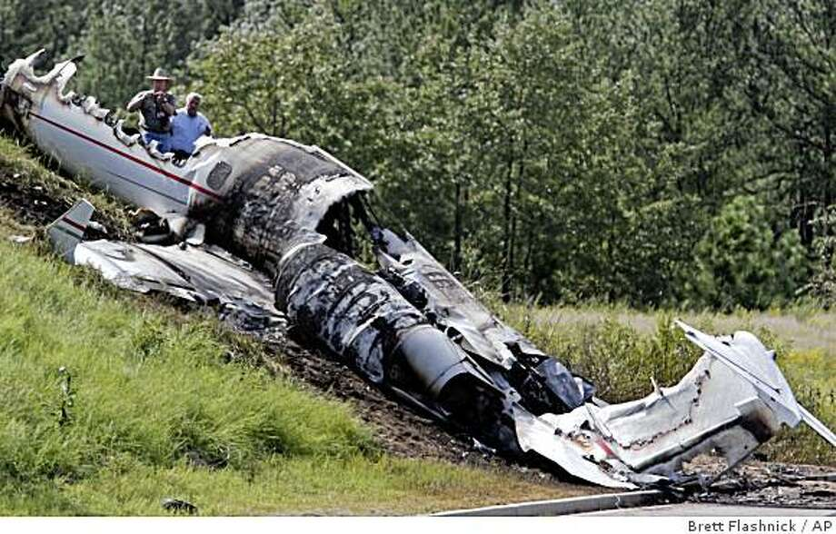 Investigators look over the debris left by the Learjet that was carrying former Blink 182, drummer, Travis Barker, and Adam Goldstein, also know as DJ-AM, on the outskirts of the Columbia Metropolitan Airport, Saturday, Sept. 20, 2008, in Columbia, S.C.  Barker and Goldstein were critically injured, and two other passengers and two crew members were killed.  (AP Photo/Brett Flashnick) Photo: Brett Flashnick, AP
