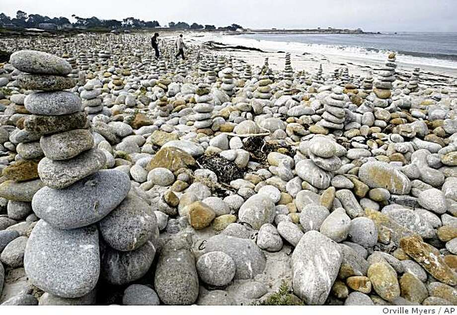 People walk to the beach through the stone art at the beach of Spanish Bay in Pebble Beach, California on Wednesday Sept. 24, 2008. (AP Photo/Monterey County Herald, Orville Myers) Photo: Orville Myers, AP