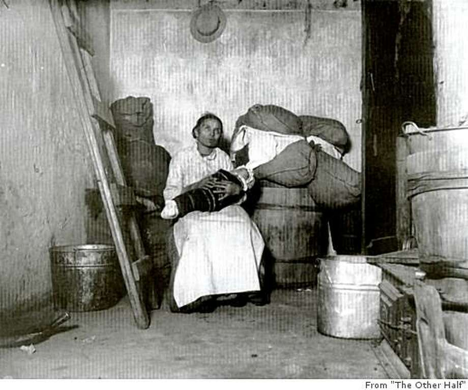 "Caption from the book ""The Other Half"": ""Italian mother with swaddled baby on Jersey Street.  Riis called this 'Home of an Italian Ragpicker.' "" / Photo by Jacob Riis, Courtesy of the Museum of the City of New York / From ""The Other Half"" / FOR USE WITH BOOK REVIEW ONLY Photo: From ""The Other Half"""