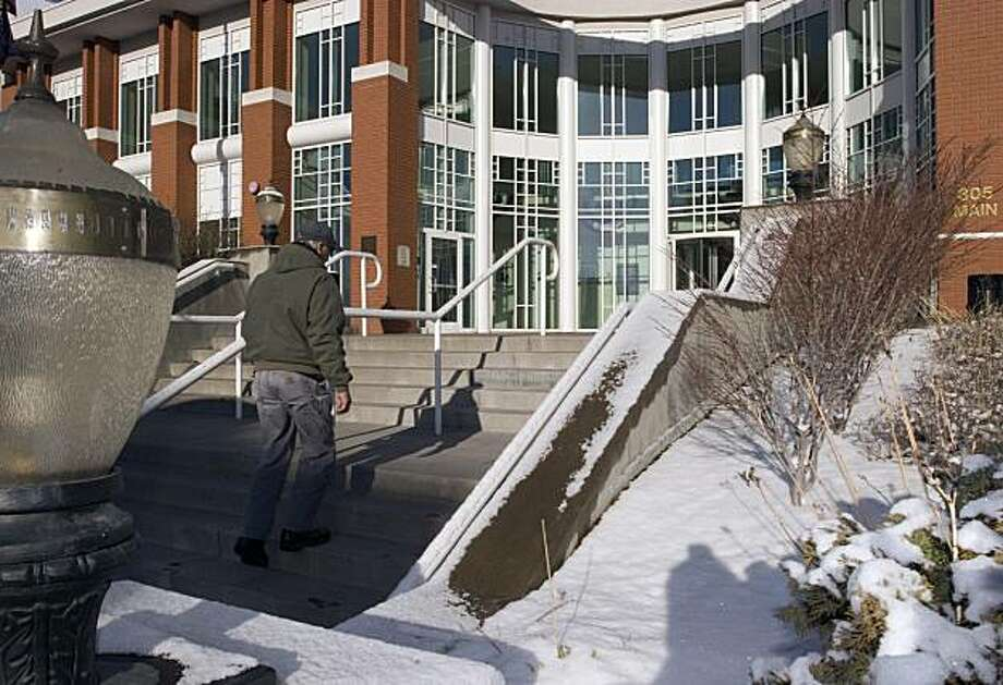 In this March 10, 2010 photo, building contractor Denl Thomas walks up the stairs at the Klamath County administration building in Klamath Falls, Ore., where sidewalks heated by geothermal energy keep snow from piling up. With a brew pub, college campus and commercial greenhouses all warmed by heat from deep within the earth, Klamath Falls serves as a model for a fledgling new green energy source that is gaining steam with the help of $338 million in federal stimulus money. Photo: Jeff Barnard, AP