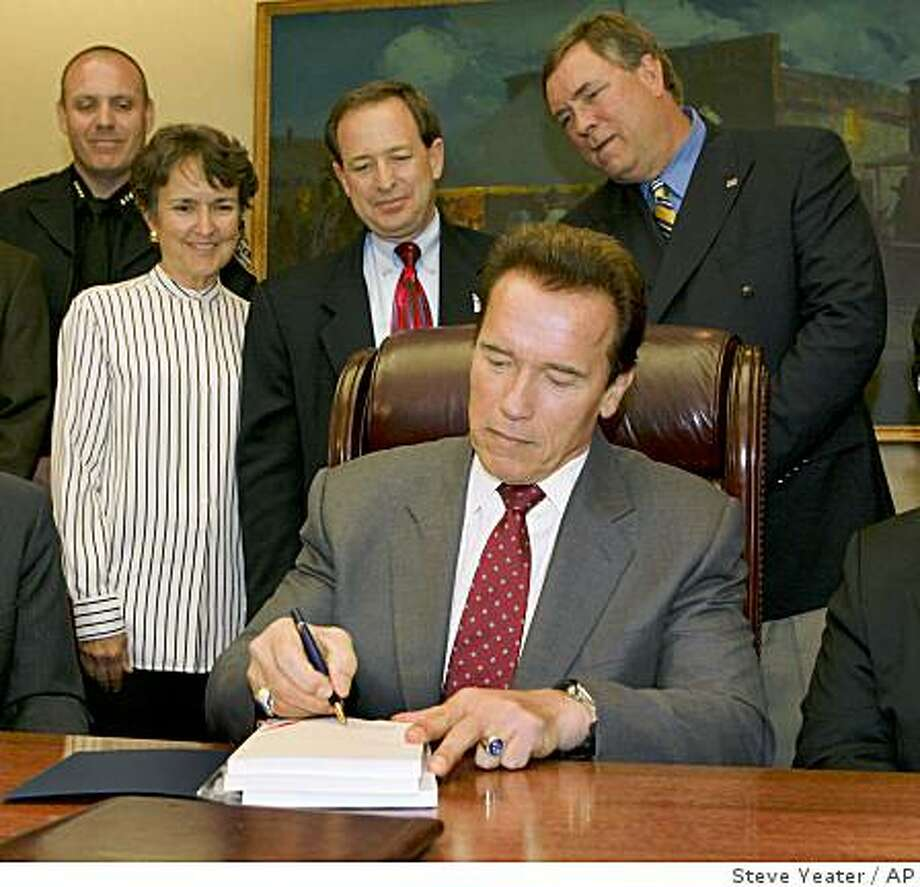 California Gov. Arnold Schwarzenegger signs the 2008-2009 state budget as representatives from local governments look on during a small ceremony in his office at the Capitol in Sacramento, Calif., on Tuesday, Sept. 23, 2008.(AP Photo/Steve Yeater) Photo: Steve Yeater, AP