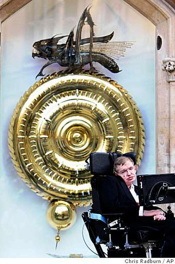 """Professor Stephen Hawking unveils The Corpus Clock, seen behind him, a new installation at Corpus Christi College in Cambridge, England, Friday, Sept. 19, 2008. Professor Stephen Hawking, author of A Brief History of Time, was guest of honour at a ceremony to mark the creation of The Corpus Clock, which cost more than 1 million pounds (US$1.8 million) to build  and erect in Cambridge. The """"Corpus clock"""" is the brainchild of inventor John Taylor, who used his own money to build it, in part to pay homage to the genius of John Harrison, the Englishman who in 1725 invented the """"grasshopper"""" escapement _ a mechanical device that helps regulate a clock's movement. Making a visual pun on the grasshopper image, Taylor has designed a fantasy version of a grasshopper at the top of the clock face, and uses this beast _ with its long needle teeth and barbed tail _ as an integral part of the clockworks. Its jaws begin to open halfway through a minute, then snap shut at 59 seconds. The creature's eyes, usually a dull green, occasionally flash bright yellow. The oversize grasshopper is called a chronophage, or """"time eater.""""  (AP Photo/Chris Radburn/PA)  **  UNITED KINGDOM OUT NO SALES NO ARCHIVE  ** Photo: Chris Radburn, AP"""