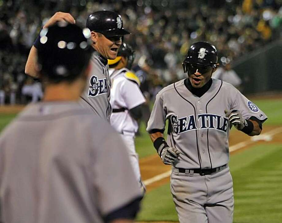Ichiro Suzuki, right, and Rob Johnson celebrate Ichiro's run in the top of the ninth. The Mariners won, 5-3. Oakland Athletics played the Seatte Mariners for their opening day at the Oakland-Alameda County Coliseum in Oakland, Calif., on Monday, April 4, 2010. Photo: Carlos Avila Gonzalez, The Chronicle