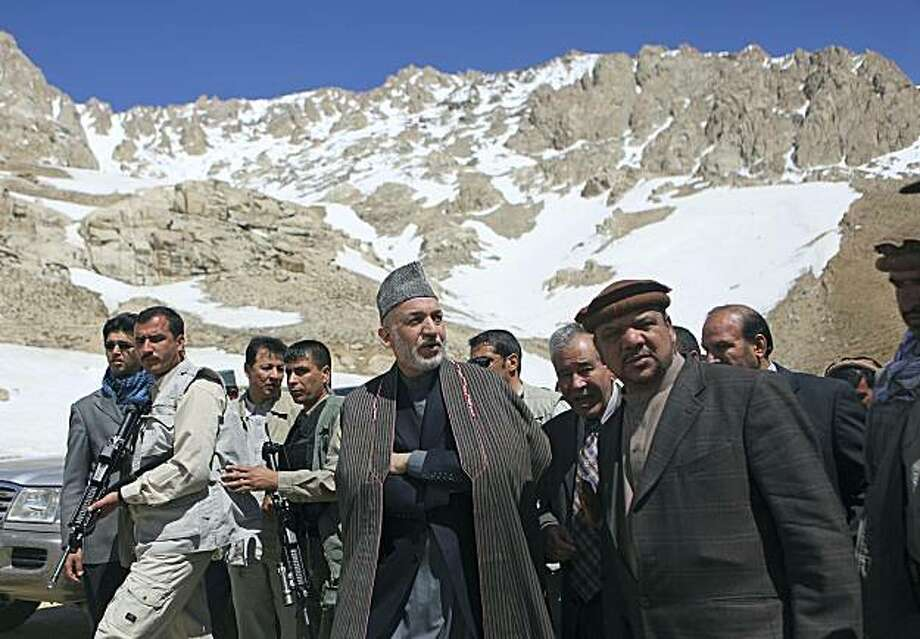 Afghan President Hamid Karzai, center, walks along with  First Vice President Muhammad Qasim Fahim, right, during his visit to an avalanche site in the Salang Pass, north of Kabul, Afghanistan, Wednesday, March 31, 2010. More then 165 people were killed last month in an avalanche at Salang Pass. Photo: Rafiq Maqbool, AP