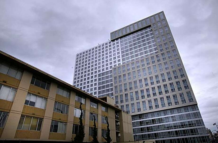 The shiny new Trinity Tower on Mission Street on an overcast day Thursday February 4, 2010 in San Francisco, Calif. dwarfs the old apartment building (left) which will ultimately be demolished. Photo: Brant Ward, The Chronicle