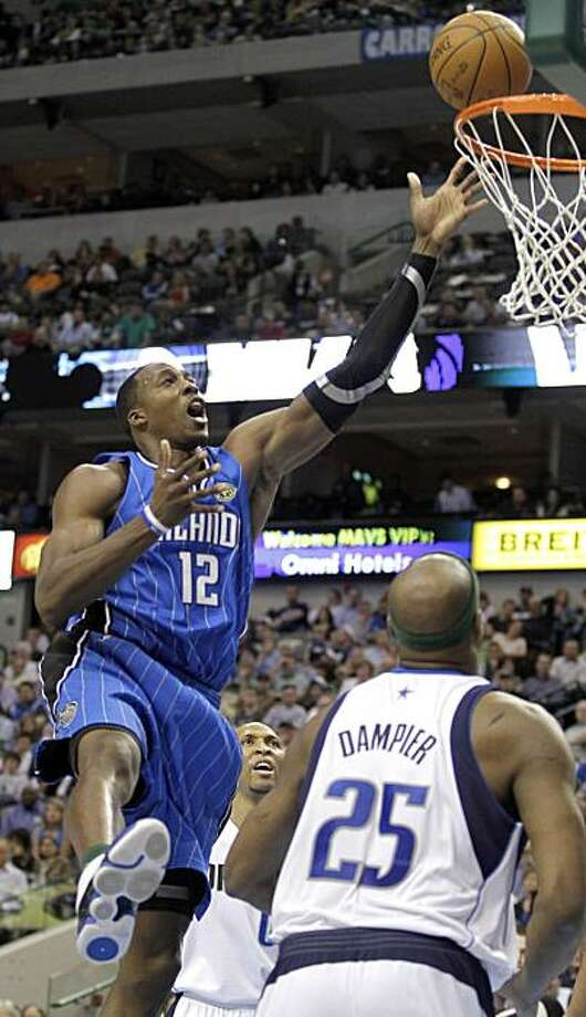Orlando Magic center Dwight Howard (12) lays in the ball over Dallas Mavericks center Erick Dampier (25) during the first quarter of their NBA basketball game, Thursday, April 1, 2010, in Dallas. Photo: Tim Sharp, AP