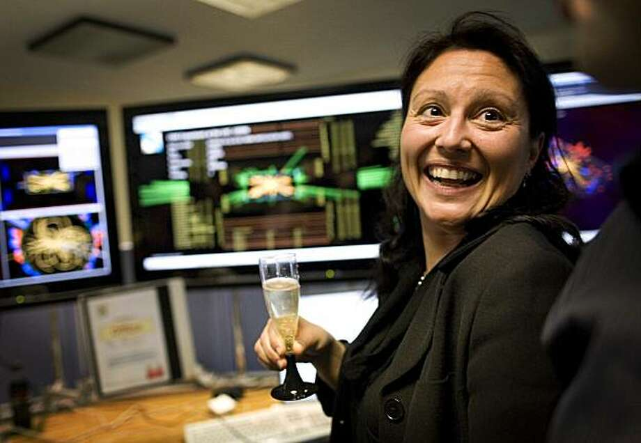 A scientist of the European Organization for Nuclear Research, CERN, celebrates with champagne in the SMS experiment control room at their headquarter outside Geneva, Switzerland, Tuesday, March 30, 2010.  The $10 billion Large Hadron Collider directed two proton beams into each other at three times more force than ever before, Tuesday, as part of its ambitious bid to reveal details about theoretical particles and microforces. Photo: Anja Niedringhaus, AP