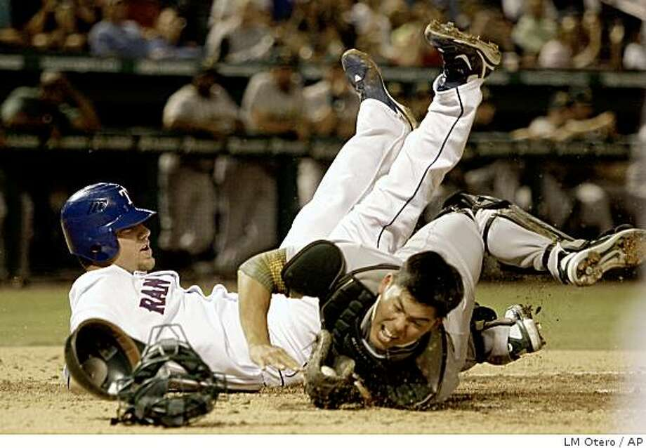 Oakland Athletics catcher Kurt Suzuki, right, hangs on to the ball after he was knocked over at home plate by Texas Rangers' Chris Davis during the second inning of a baseball game in Arlington, Texas, Monday, Sept. 22, 2008. Davis tried score on a single by German Duran. (AP Photo/LM Otero) Photo: LM Otero, AP