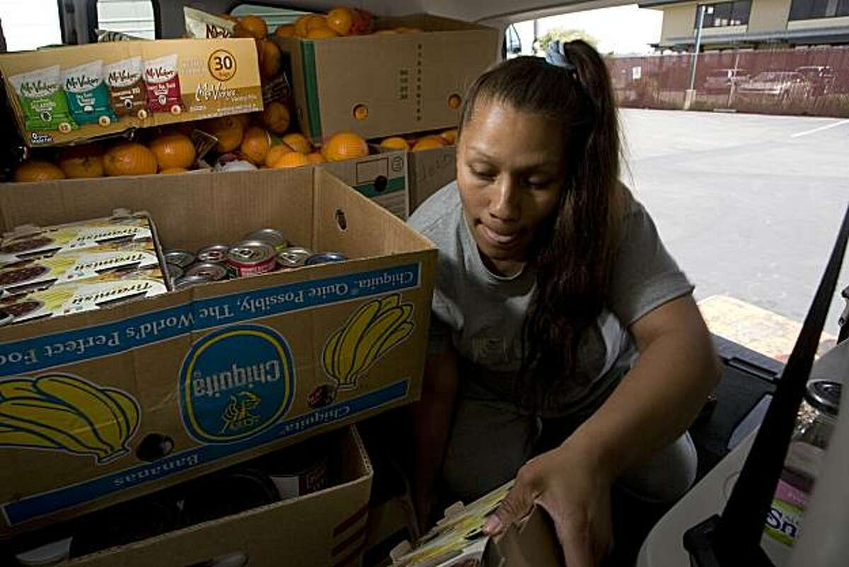 Sherri Martinez packs up food purchased at The Alameda County Food Bank in Oakland on Thursday, April 1, 2010 to be handed out from the food pantry at Templo de la Cruz in Hayward including boxes of free oranges. The Alameda County Food Bank participates in the Farm to Family program that helps to reclaim food that would have been tossed by farmers. The food bank gives the reclaimed produce away for free. Kat Wade / Special to the Chronicle