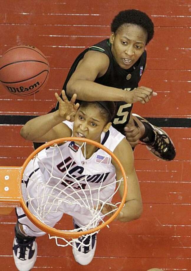 Connecticut's Maya Moore gets hit by Baylor's Shanay Washington, top, while shooting in the first half of a semifinal in the Final Four of the NCAA women's college basketball tournament Sunday, April 4, 2010, in San Antonio. Photo: Eric Gay, AP