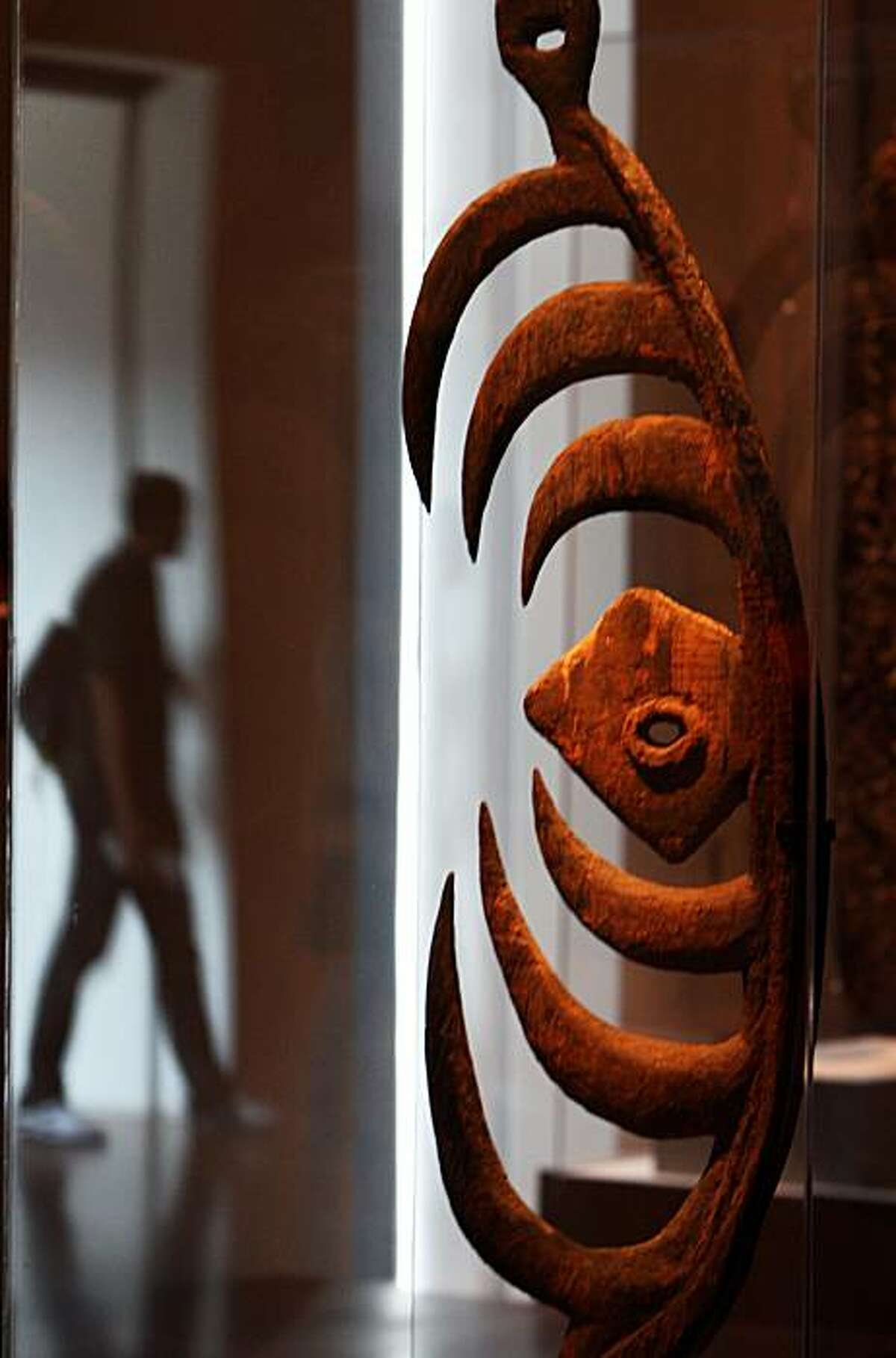 A visitor to the de Young Museum is reflected off the case housing a Cult Object, made by Bahinemo People from the Hunstein Mountains dated 18th-19th century. John Friede - a de Young trustee, donated the Jolika Collection of New Guinean art to the de Young Museum. The collection is now embroiled in an ownership dispute because a week after he gave the collection to the museum, he signed a paper giving the collection to his siblings who want to sell it off. There may also be a dispute from Papua New Guinea who might lay claim that the pieces were improperly taken from the country. Photographed in San Francisco Friday Sept 19, 2008.