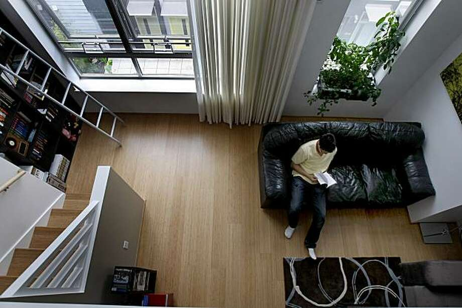 Tae Hong relaxes in his new home in West Oakland. Tae Hong made an offer on a condominium last year, but just moved in because no lender would write a mortgage until 70 percent of the units were sold. Photo: Brant Ward, The Chronicle