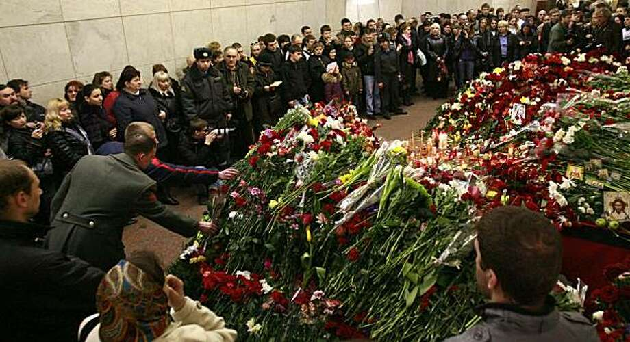 Russians stand near a growing mound of flowers commemorating the victims of the metro blasts inside the Lubyanka metro station in Moscow on March 30, 2010. Grieving Muscovites added to heaps of flowers and placed photographs of the dead under memorial plaques at the stations. Flags at government buildings flew at half mast and television channels cancelled entertainment programmes. Photo: Str, AFP/Getty Images