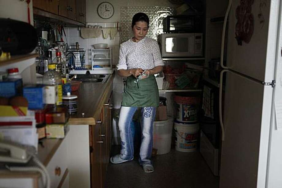 "Haddie Lin, who has been a housekeeper at the Grand Hyatt for 14 years, stand in her apartment kitchen making food the week on Tuesday March 23, 2010 in San Francisco, Calif. Lin, a single mother soon thinks she may soon be settled with college bills for her son says she 's very concerned with potential rising costs of health care benefits. ""Even just $10 a month I have to budget for,"" she said. ""Every penny counts. If I need to pay an increase I have to cut another expense."" Photo: Mike Kepka, The Chronicle"