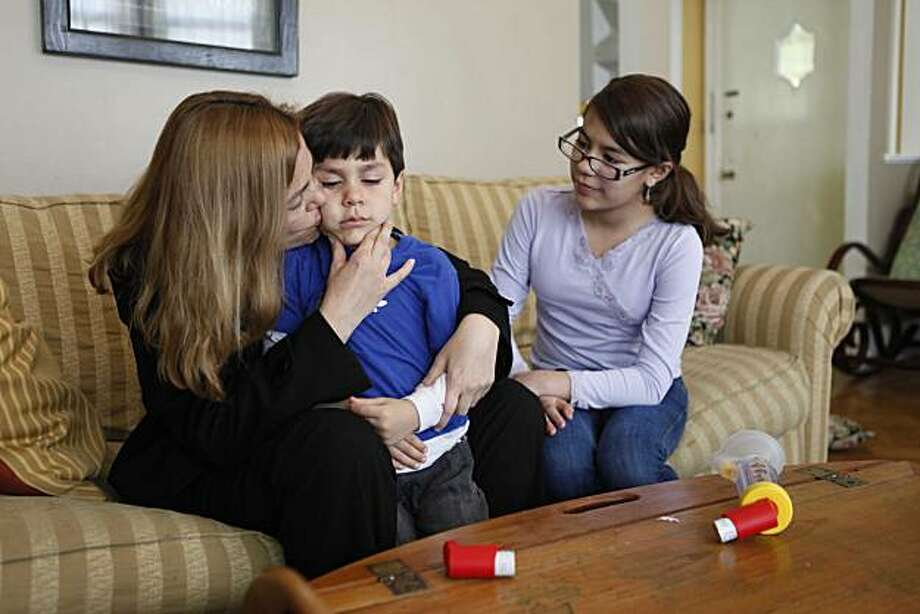 Gladys Soto hugs her son William Holder-Soto, 4in their living room, as his big sister Giovanna Soto, 11, watches, on Tuesday March 30, 2010 in San Francisco, Calif. William was diagnosed with asthma a year ago and now because of Obama's new health care plan, starting in September, he won't be denied health care for reason of pre-existing condition. Photo: Mike Kepka, The Chronicle