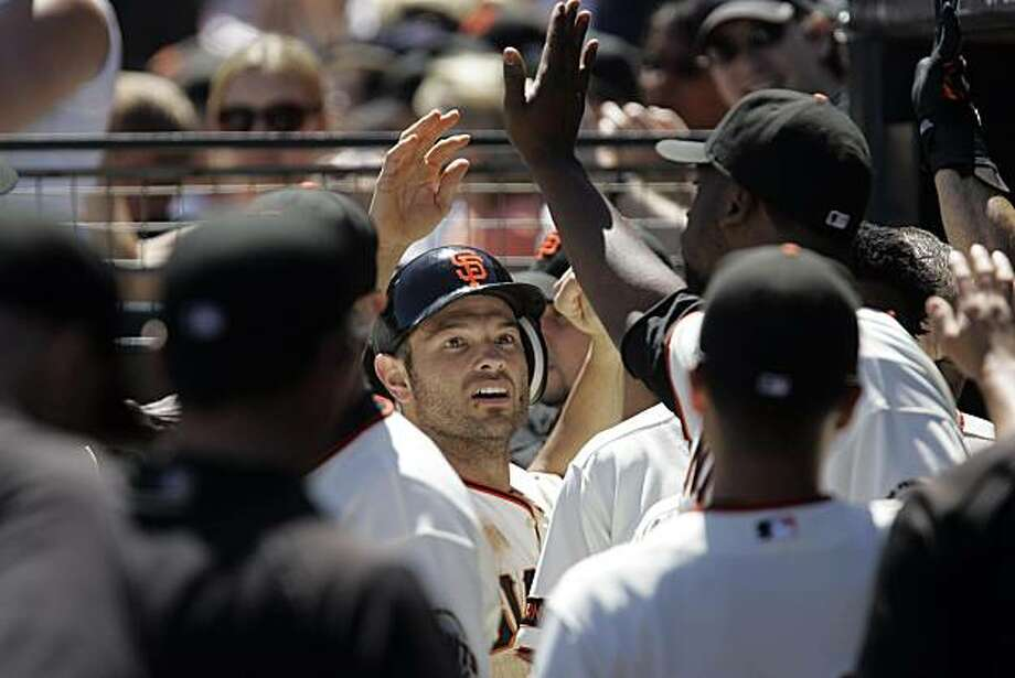 Freddy Sanchez is congratulated in the Giants dugout after scoring in the 5th inning of the 4-2 Giants win over the Los Angeles Dodgers at AT&T park in San Francisco, Calif., on Wednesday, August 14, 2009. Photo: Scot Tucker, The Chronicle