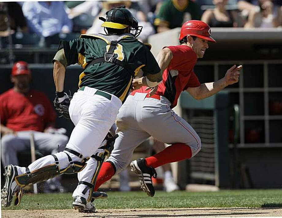 Oakland Athletics' Kurt Suzuki, left, chases Cincinnati Reds' Chris Burke after Burke was caught stealing home in the third inning of a spring training baseball game in Phoenix, Wednesday, March 31, 2010. Photo: Jeff Chiu, AP