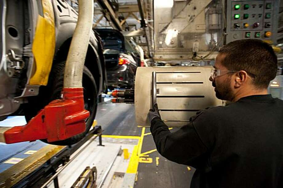 A NUMMI plant worker guides machinery into position that automatically screws in lug nuts to a Toyota Corolla as it passes by on the assembly line on March 4, 2010, in Fremont, CA. Photo: Chad Ziemendorf, Special To The Chronicle