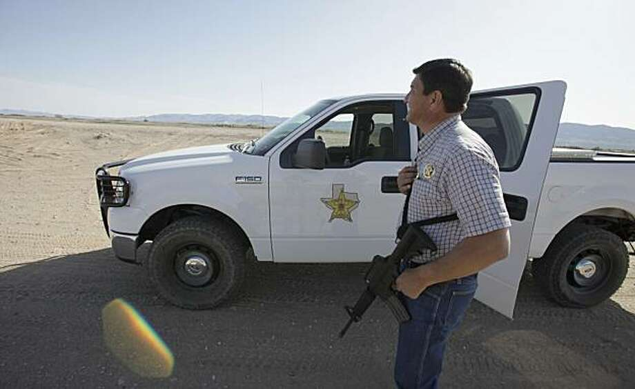 In this March 25, 2010 photo, Hudspeth County Sheriff's Lt. Robert Wilson scans the nearby border at  Fort Hancock, Texas. Fear has settled over this border town of 1,700, about 50 miles southeast of Ciudad Juarez, Mexico, epicenter of that country's bloody drug war. Mexican families fleeing the violence have moved here or just sent their children, and authorities and residents say gangsters have followed them across the Rio Grande to apply terrifying, though so far subtle, intimidation. Photo: LM Otero, AP